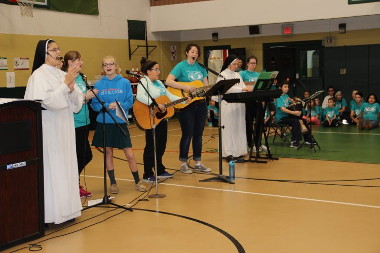 sisters of Mary and students singing in gymnasium