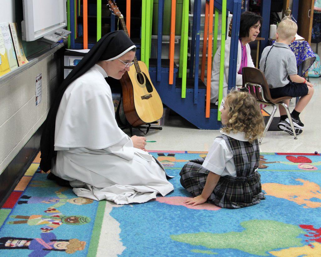 nun teaching student in elementary class