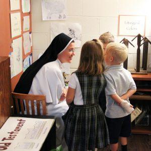 nun talking to elementary students