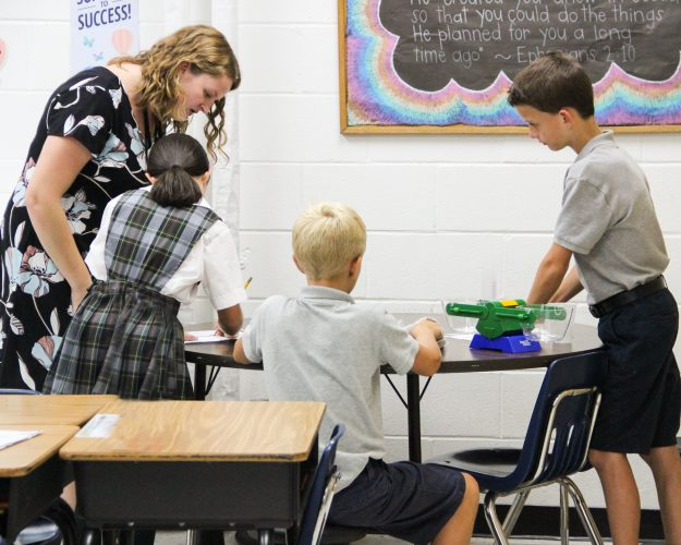 teacher assisting students at st. michael school